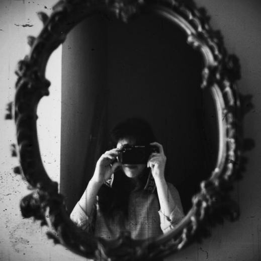 grayscale-photo-of-woman-taking-photo-of-round-mirror-3739059